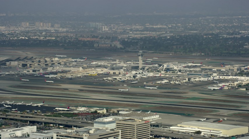 8K stock footage aerial video tracking a plane taking off from LAX, cloudy, Los Angeles, California Aerial Stock Footage | AX0157_004