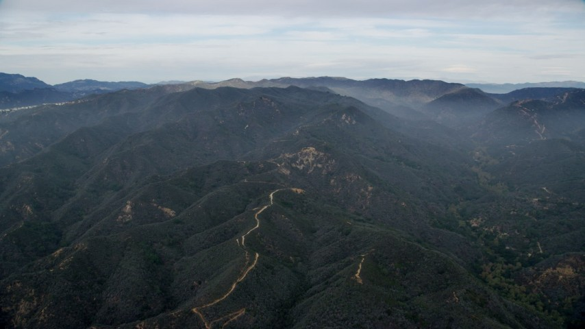 8K stock footage aerial video approach the Santa Monica Mountains with marine layer in California Aerial Stock Footage | AX0157_014