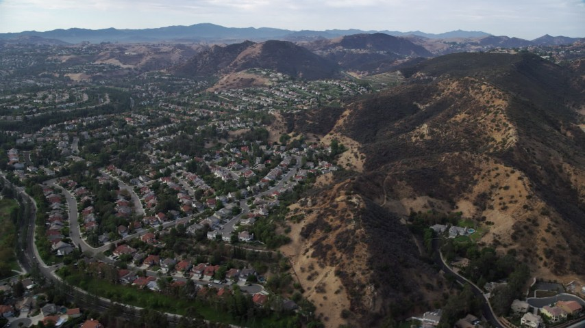 8K stock footage aerial video flying by tract homes and hills in West Hills, California Aerial Stock Footage | AX0157_037