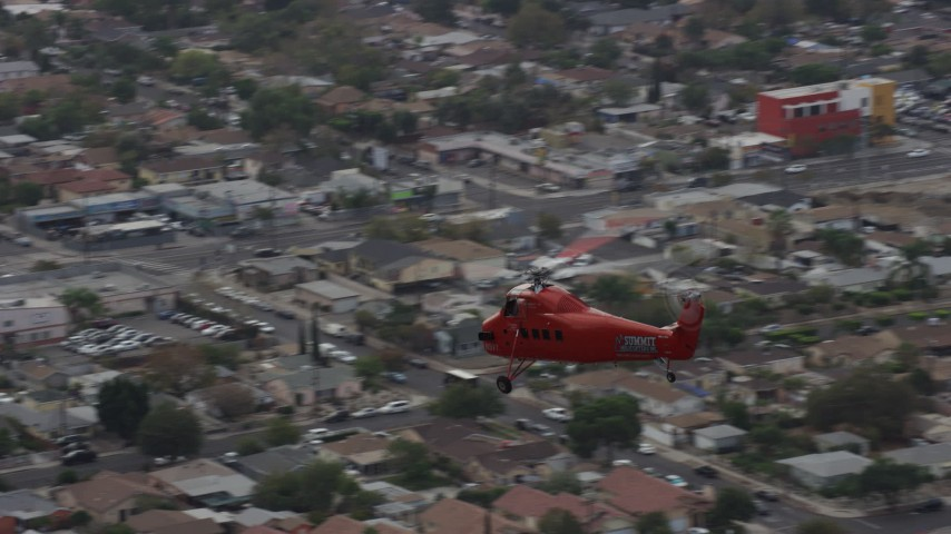 8K stock footage aerial video tracking a Sikorsky S58T flying over Pacoima, California Aerial Stock Footage AX0157_087 | Axiom Images
