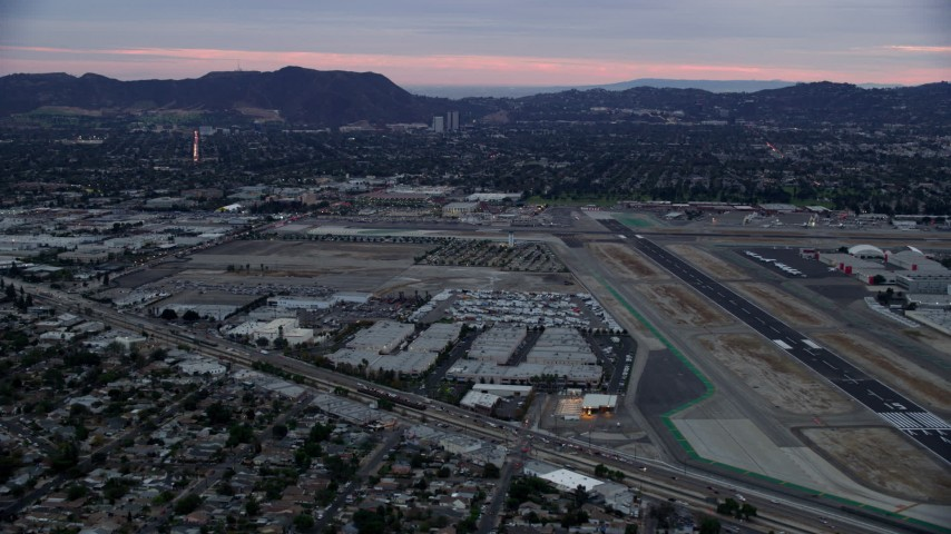 8K stock footage aerial video dying by Burbank airport at twilight, Burbank, California Aerial Stock Footage | AX0158_001
