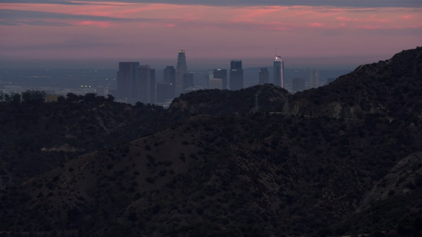 8K stock footage aerial video of Downtown Los Angeles seen from behind a hill, twilight, California Aerial Stock Footage | AX0158_004