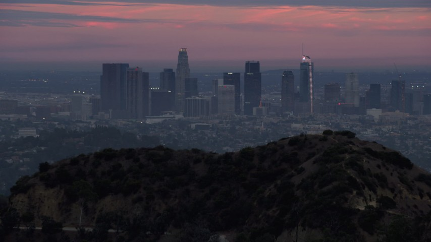 8K stock footage aerial video reveal of Downtown Los Angeles from behind a hill, twilight, California Aerial Stock Footage | AX0158_005