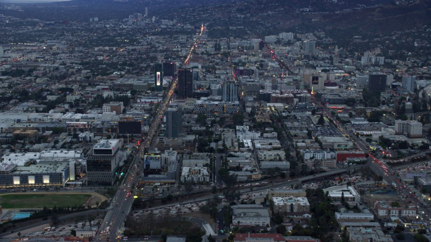 8K stock footage aerial video approaching Sunset Boulevard and neighboring businesses, twilight, Hollywood, California Aerial Stock Footage | AX0158_015