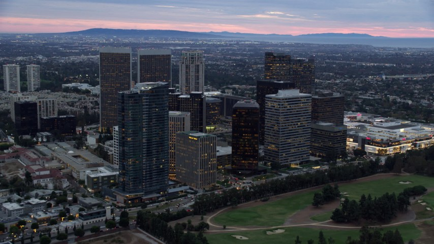 8K stock footage aerial video passing by office buildings and skyscrapers at twilight, Century City, California Aerial Stock Footage | AX0158_024