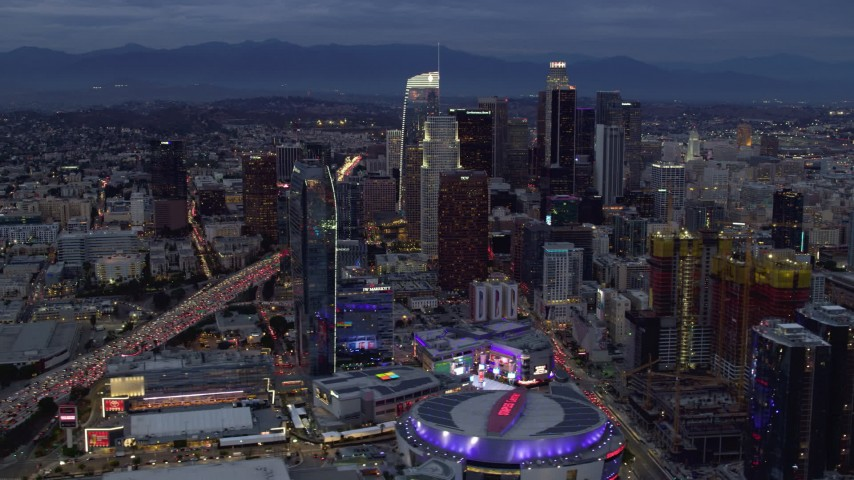 8K aerial video orbiting Downtown Los Angeles skyscrapers, Interstate 110 and Staples Center at twilight, California Aerial Stock Footage | AX0158_045