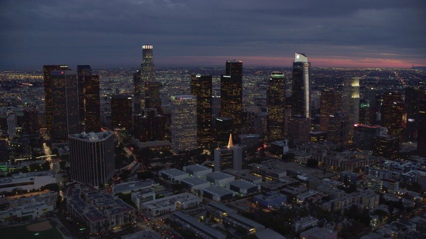 8K stock footage aerial video passing skyscrapers at twilight in Downtown Los Angeles, California Aerial Stock Footage | AX0158_052