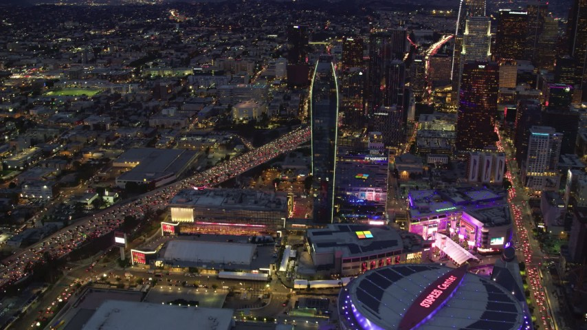 8K stock footage aerial video flying by Staples Center, skyscrapers, and heavy 110 traffic at twilight, Downtown Los Angeles, California Aerial Stock Footage | AX0158_061