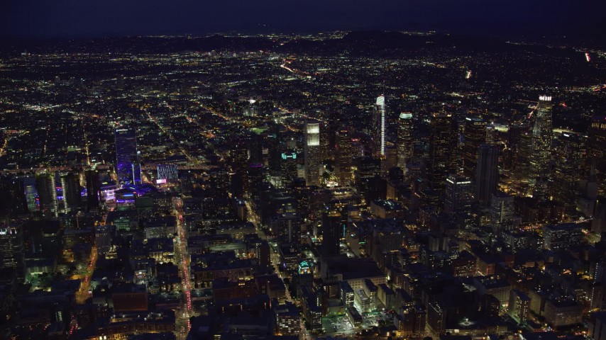 8K stock footage aerial video flying by the tall towers and lights of Downtown Los Angeles, California at night Aerial Stock Footage | AX0158_080