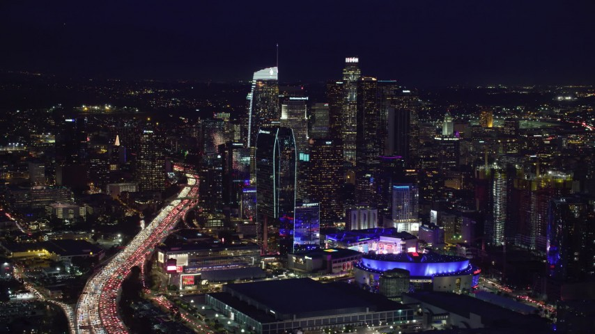 8K stock footage aerial video of 110 traffic by skyscrapers and Staples Center at night, Downtown Los Angeles, California Aerial Stock Footage | AX0158_091