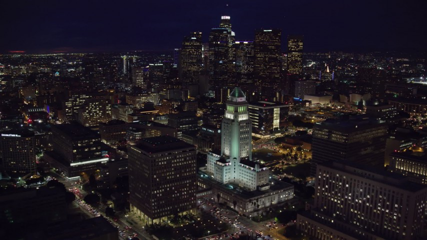 8K stock footage aerial video orbiting City Hall at night near skyscrapers in Downtown Los Angeles, California Aerial Stock Footage | AX0158_102