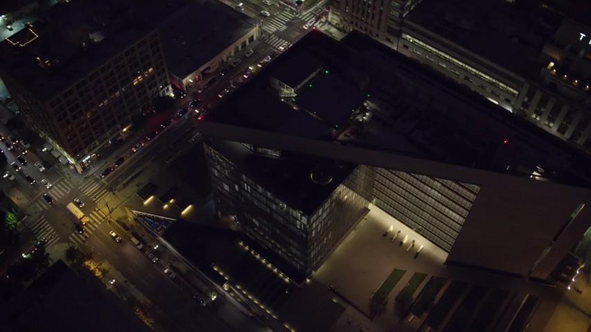 8K stock footage aerial video of a bird's eye and reverse view of LAPD headquarters at night in Downtown Los Angeles, California Aerial Stock Footage | AX0158_104
