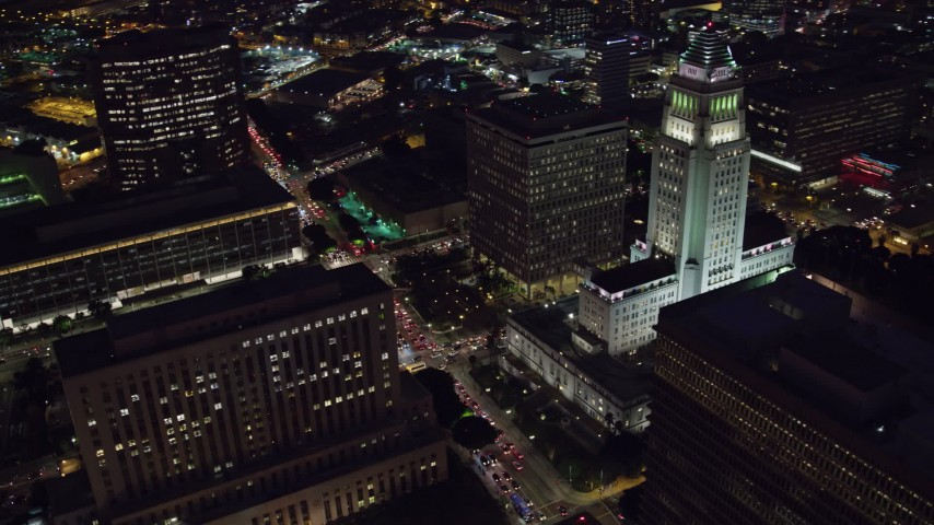 8K stock footage aerial video flying away from LA City Hall at night in Downtown Los Angeles, California Aerial Stock Footage | AX0158_107