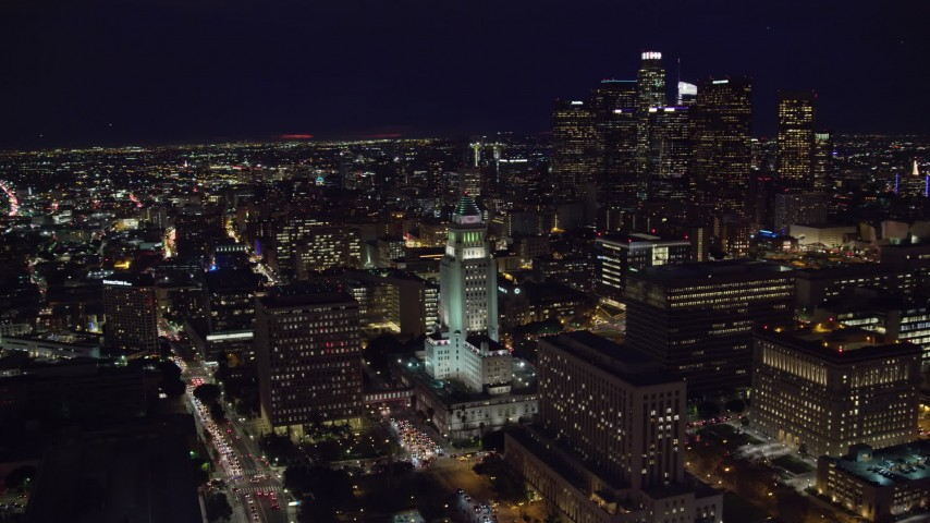 8K stock footage aerial video orbiting LA City Hall to reveal skyscrapers at night in Downtown Los Angeles, California Aerial Stock Footage AX0158_108 | Axiom Images