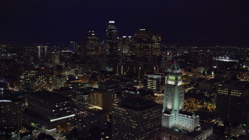 8K stock footage aerial video of Downtown skyscrapers seen while flying by City Hall at night in Downtown Los Angeles, California Aerial Stock Footage | AX0158_109
