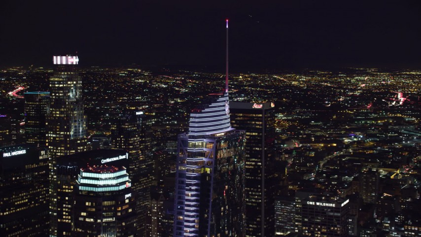 8K stock footage aerial video circling the top of Wilshire Grand Center at night in Downtown Los Angeles, California Aerial Stock Footage | AX0158_113