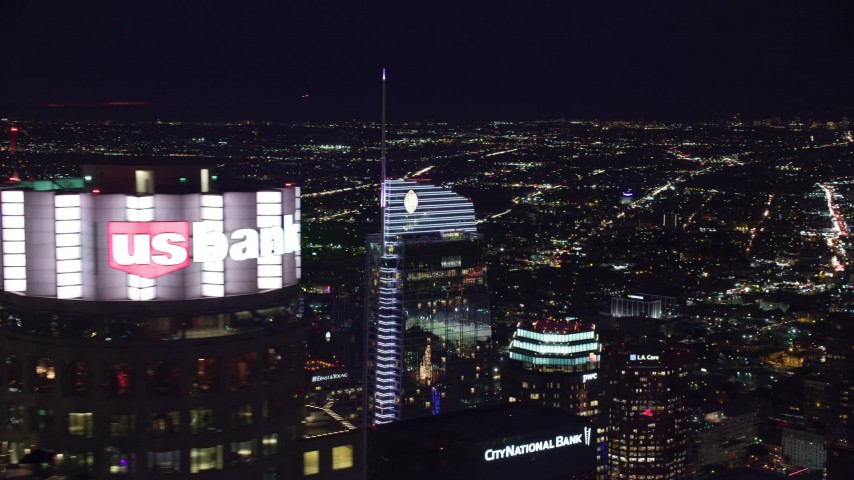 8K stock footage aerial video orbiting the top of Wilshire Grand Center and reveal US Bank Tower at night, Downtown Los Angeles, California Aerial Stock Footage | AX0158_116