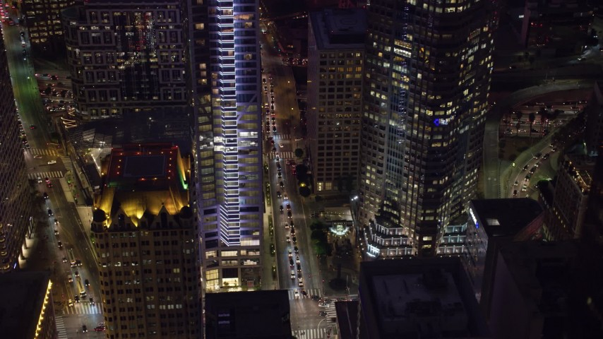 8K aerial video revealing Wilshire Blvd and base of Wilshire Grand Center at night, Downtown Los Angeles, California Aerial Stock Footage | AX0158_117