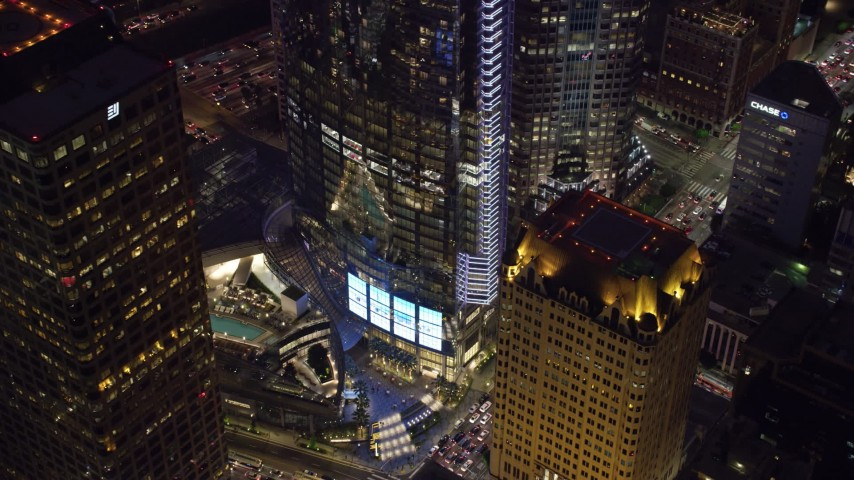 8K stock footage aerial video of a view of the base of Wilshire Grand Center at night in Downtown Los Angeles, California Aerial Stock Footage | AX0158_118