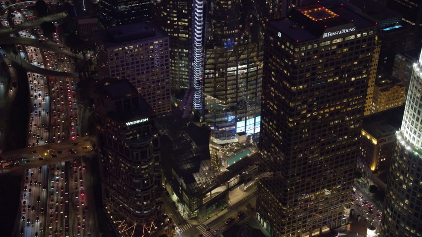 8K aerial video of the base of the Wilshire Grand Center skyscraper at night in Downtown Los Angeles, California Aerial Stock Footage | AX0158_119