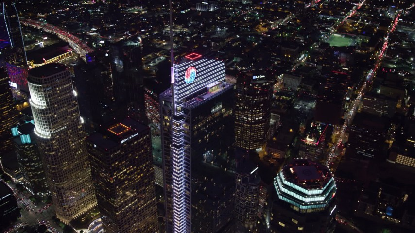 8K stock footage aerial video orbiting and tilt to a bird's eye of Wilshire Grand Center in Downtown Los Angeles, California at night Aerial Stock Footage | AX0158_122