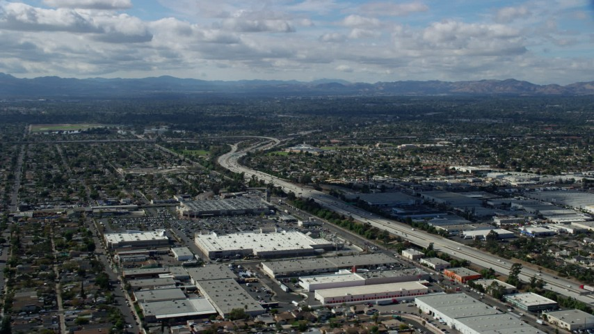 8K stock footage aerial video flying over the 118 freeway and warehouses, Pacoima, San Fernando Valley, California Aerial Stock Footage | AX0159_002