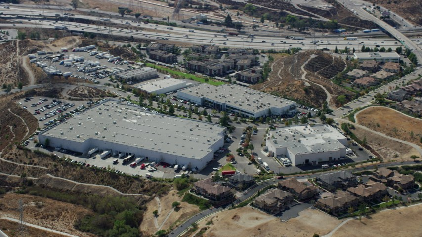 8K aerial video of a Warehouse and Industrial buildings near the interstate, Sylmar, San Fernando Valley, California Aerial Stock Footage | AX0159_008