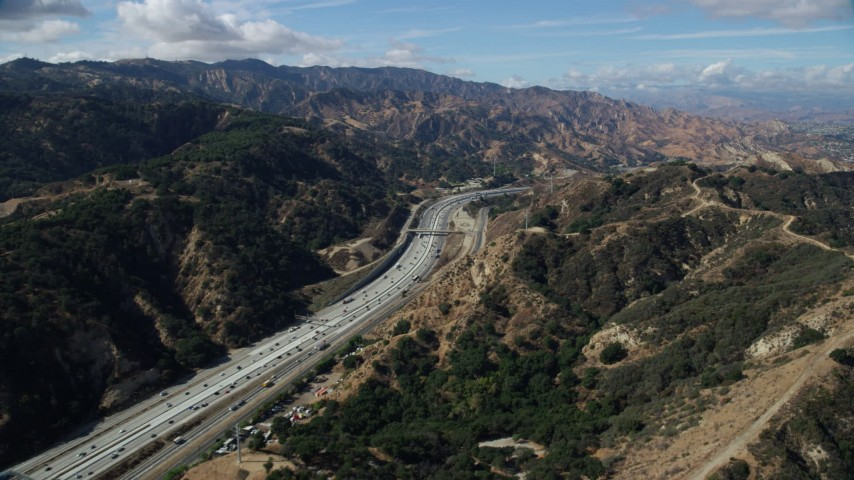 8K stock footage aerial video following light traffic on I-5 through the mountains, Santa Clarita, California Aerial Stock Footage | AX0159_010
