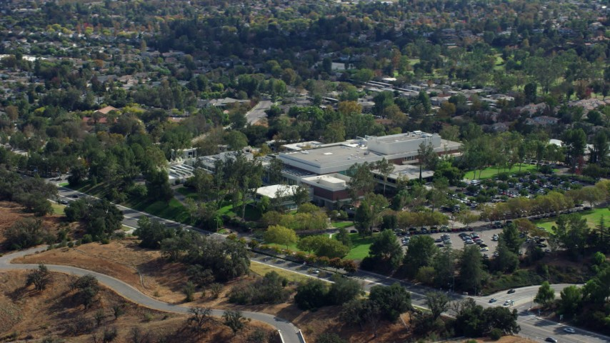 8K stock footage aerial video orbiting away from College Institute of the Arts and its parking lot, Santa Clarita, California Aerial Stock Footage | AX0159_019