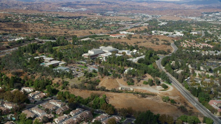 8K stock footage aerial video of a wide shot of California Institute of the Arts nestled among suburban neighborhoods, Santa Clarita, California Aerial Stock Footage | AX0159_023