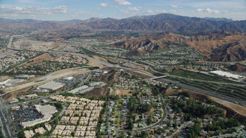 8K stock footage aerial video flying over suburban housing toward highway and mountains, Santa Clarita, California Aerial Stock Footage | AX0159_050