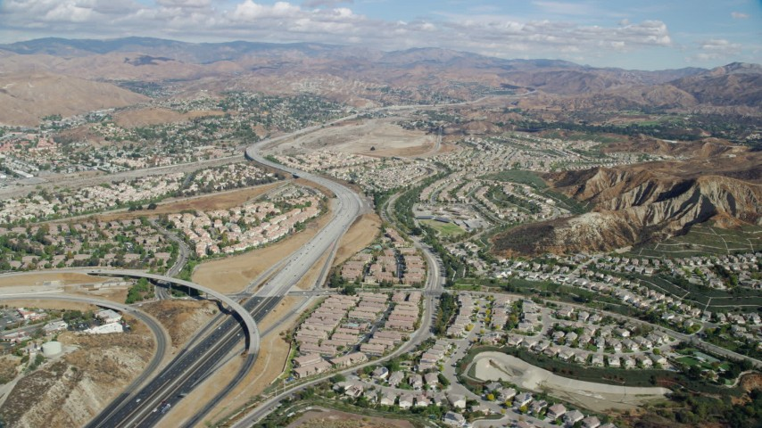 8K stock footage aerial video of suburban housing and an interchange with mountains in the distance, Santa Clarita, California Aerial Stock Footage | AX0159_051