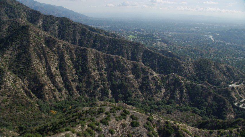 8K stock footage aerial video flying over mountain ridges with a residential community in the distance, Tujunga, California Aerial Stock Footage | AX0159_063