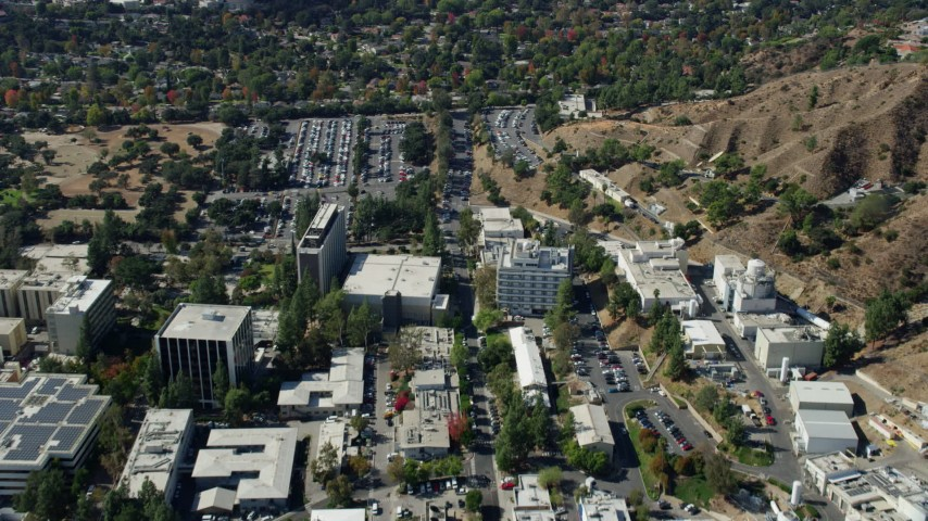 8K stock footage aerial video flying over JPL facility toward neighboring suburban houses; Pasadena, California Aerial Stock Footage | AX0159_084