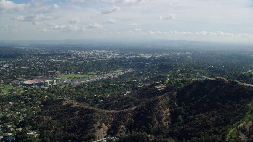 8K stock footage aerial video flying over hilltop toward residential neighborhoods below, Pasadena, California Aerial Stock Footage | AX0159_092