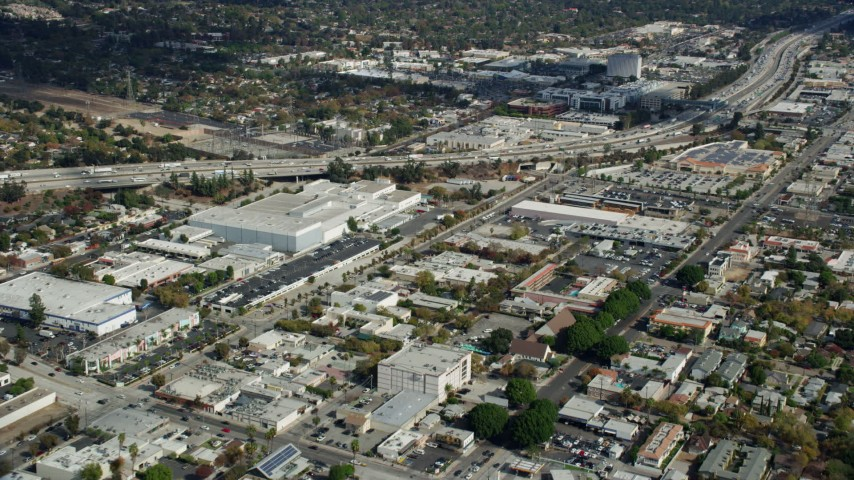 8K stock footage aerial video of office buildings and a large warehouse beside I-210 in Pasadena, California Aerial Stock Footage | AX0159_111