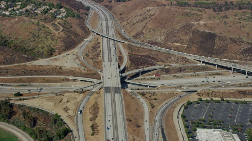8K aerial video of a reverse view of the I-10 / Hwy 57 / Hwy 71 Interchange in Pamona, California Aerial Stock Footage | AX0159_133