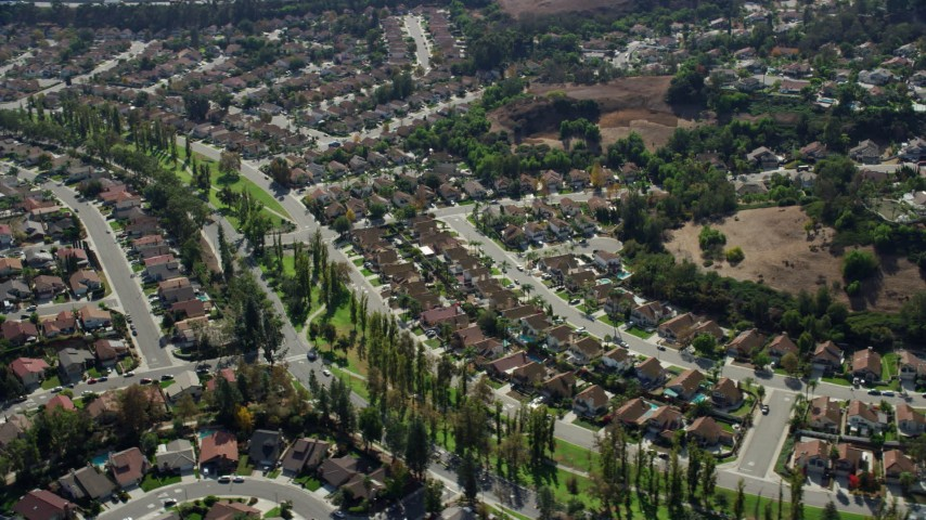 8K aerial video flying by tract homes in a peaceful neighborhood in Pamona, California Aerial Stock Footage AX0159_134