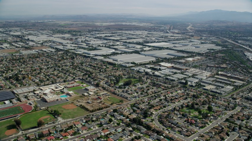 8K stock footage aerial video flying over homes and Don Antonio High School, approach warehouses, Chino, California Aerial Stock Footage | AX0159_136
