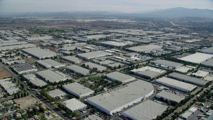 8K stock footage aerial video flying over numerous large warehouses in Chino, California Aerial Stock Footage | AX0159_137