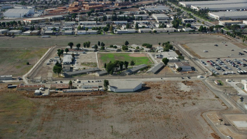 8K stock footage aerial video approaching the California Institution for Men prison in Chino, California Aerial Stock Footage | AX0159_142