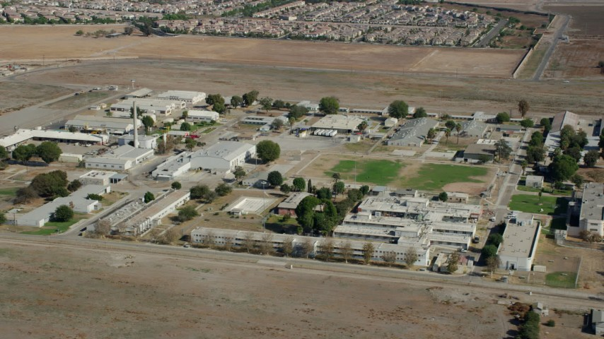 8K stock footage aerial video passing by the California Institution for Men prison in Chino, California Aerial Stock Footage | AX0159_144