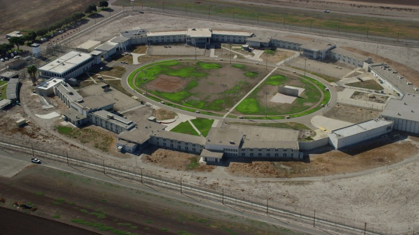 8K stock footage aerial video orbiting the East Yard of the California Institution for Men in Chino, California Aerial Stock Footage | AX0159_148