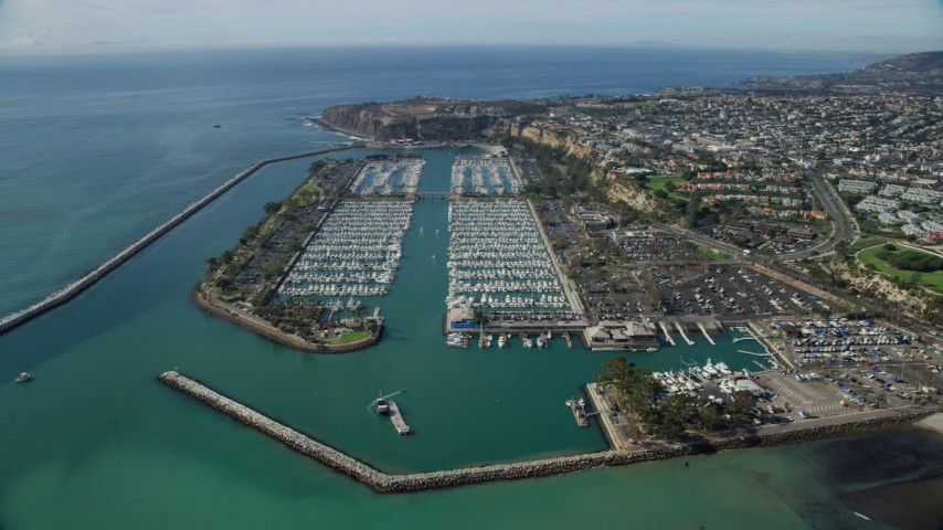 8K stock footage aerial video of breakwaters around Dana Point Harbor, and seaside neighborhoods in Dana Point, California Aerial Stock Footage | AX0159_188