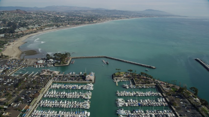 8K stock footage aerial video flying over boats at Dana Point Harbor, and approach the shore in Dana Point, California Aerial Stock Footage | AX0159_194