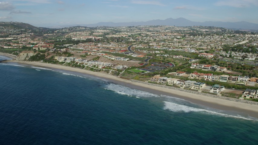 8K stock footage aerial video of beachfront mansions by Dana Strands Beach in Dana Point, California Aerial Stock Footage | AX0159_200