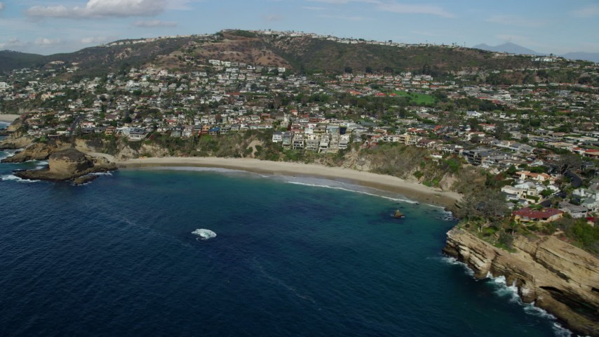 8K aerial video flying by homes beside Three Arch Bay Beach in Laguna Beach, California Aerial Stock Footage | AX0159_203