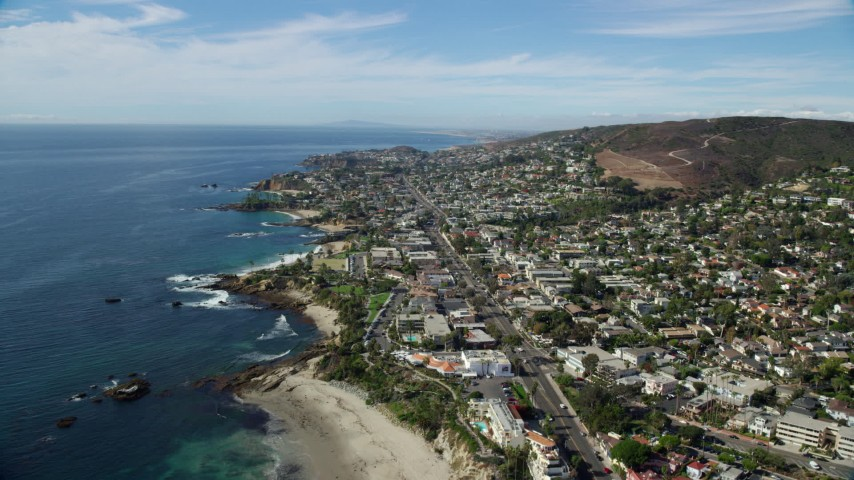8K aerial video flying over beach toward highway surrounded by houses; Laguna Beach, California Aerial Stock Footage | AX0159_210