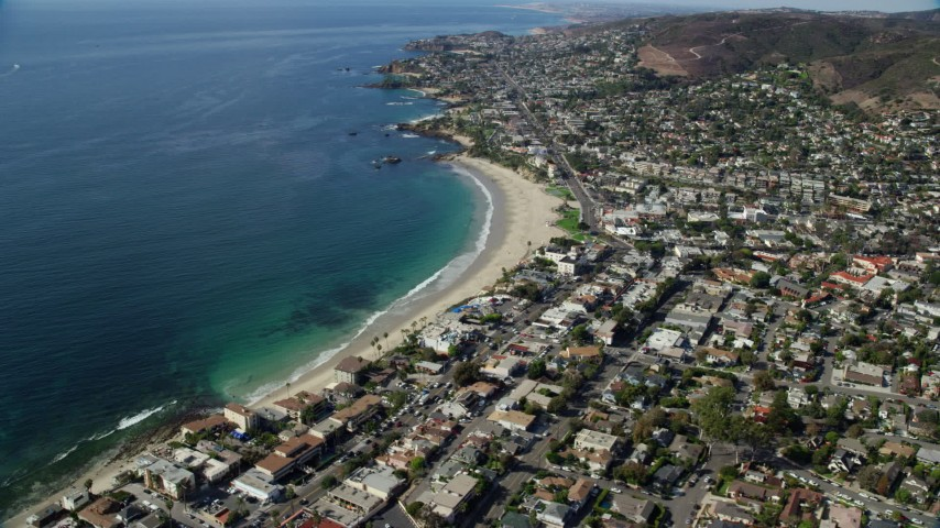 8K aerial video flying away from beach and over coastal community, Laguna Beach, California Aerial Stock Footage | AX0159_214