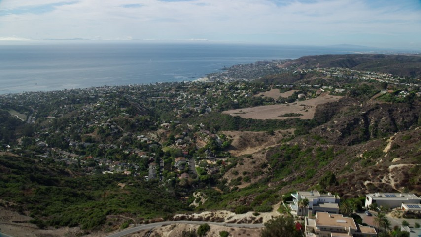 8K aerial video flying over hill to reveal coastal community below, Laguna Beach, California Aerial Stock Footage | AX0159_215